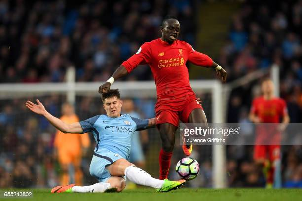 John Stones of Manchester City tackles Sadio Mane of Liverpool during the Premier League match between Manchester City and Liverpool at Etihad...