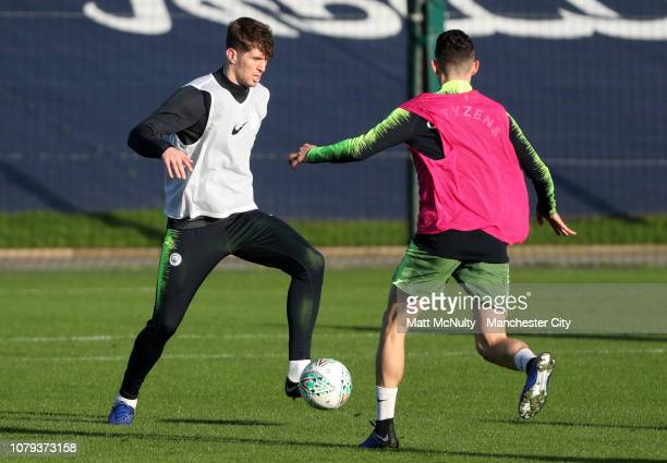 John Stones of Manchester City takes on Phil Foden during the training session at Manchester City Football Academy on January 8 2019 in Manchester...