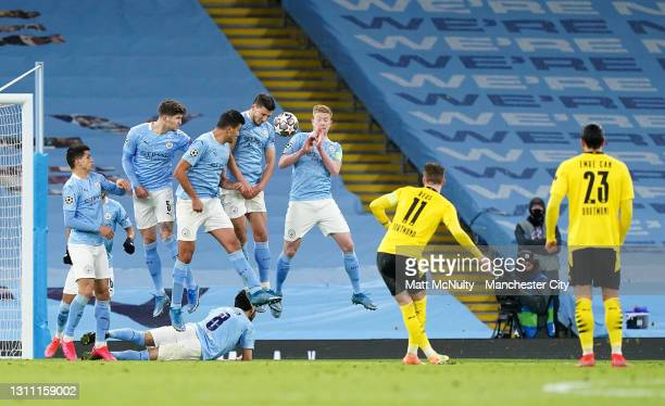 John Stones, Rodrigo, Ruben Dias and Kevin De Bruyne of Manchester City defend a free-kick from Marco Reus of Borussia Dortmund during the UEFA...