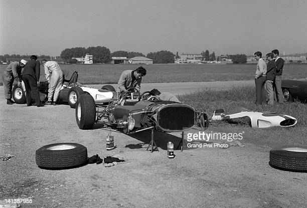 John Surtees and driver of the North American Racing Team Ferrari 158 Ferrari V8 talks with Ferrari Technical Director Mauro Forghieri during at test...