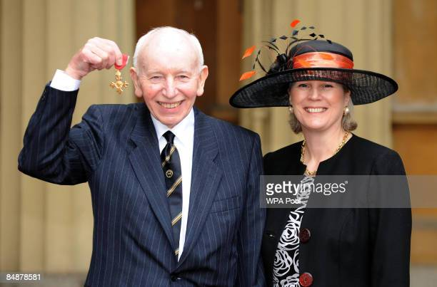 John Surtees and his wife Jane Surtees pose for photographs after he was awarded an OBE by Queen Elizabeth II at Buckingham Palace on February 18...