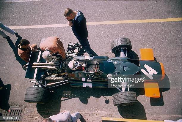 John Surtees in his BRM at the British Grand Prix Silverstone Northamptonshire 1969 Mechanics work on the car while Surtees sits in the cockpit John...
