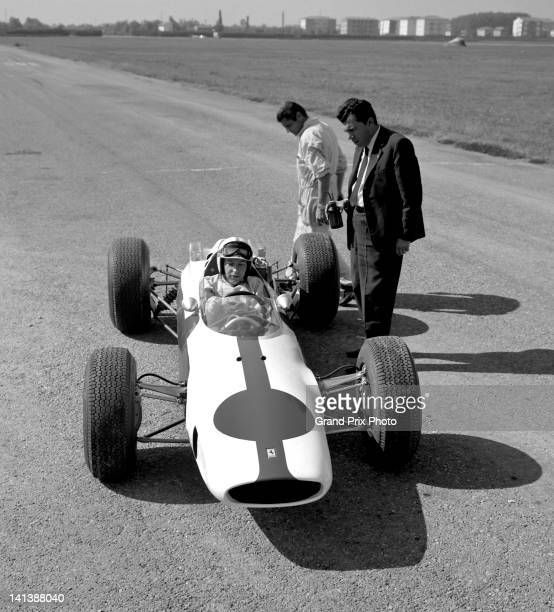 John Surtees of Great Britain sits aboard the North American Racing Team Ferrari 158 Ferrari V8 during at test session in preparation for the United...