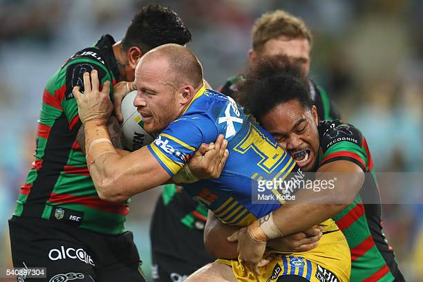 John Sutton and Siosifa Talakai of the Rabbitohs tackle Beau Scott of the Eels during the round 15 NRL match between the South Sydney Rabbitohs and...