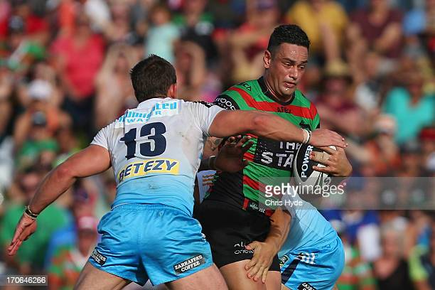 John Sutton of the Rabbitohs is tackled by Ashley Harrison of the Titans during the round 14 NRL match between the South Sydney Rabbitohs and the...