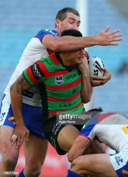 John Sutton of the Rabbitohs is tackled by Chris Houston of the Knights during the round 18 NRL match between the South Sydney Rabbitohs and the...