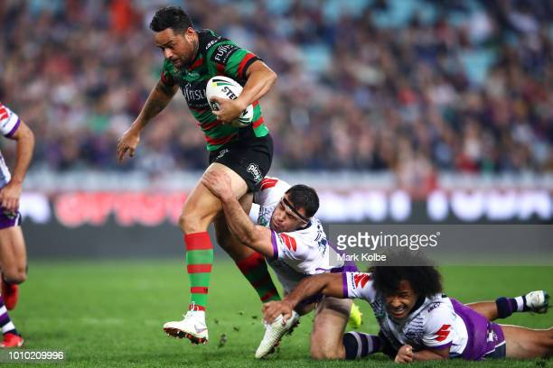 John Sutton of the Rabbitohs is tackled by Dale Finucane and Felise Kaufusi of the Storm during the round 21 NRL match between the South Sydney...