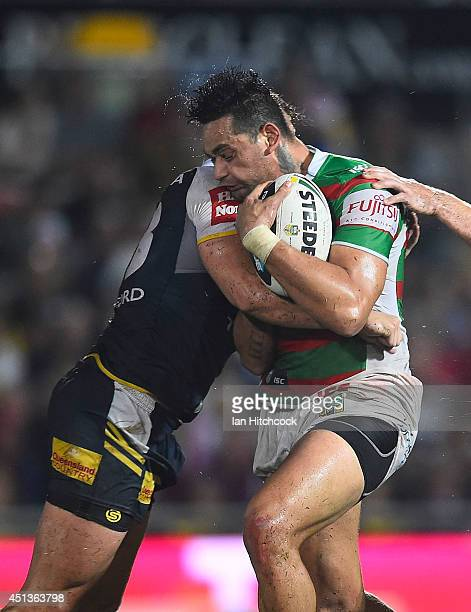 John Sutton of the Rabbitohs is tackled by Tariq Sims of the Cowboys during the round 16 NRL match between the North Queensland Cowboys and the South...
