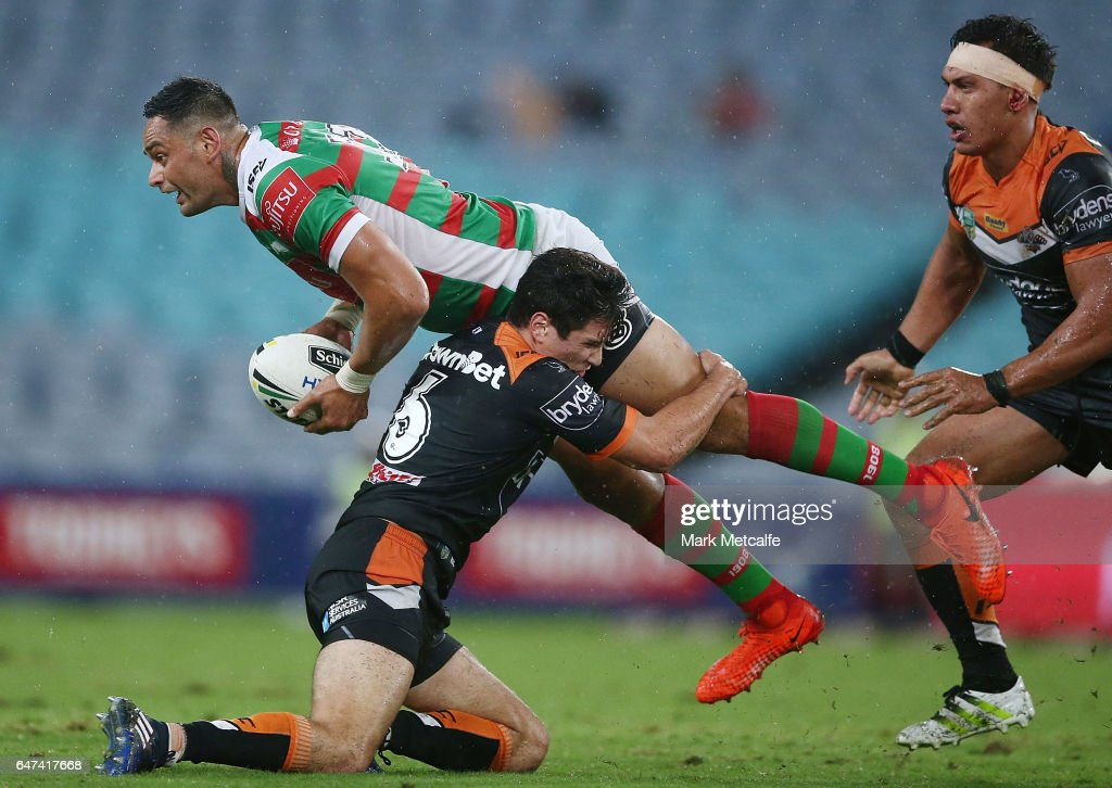 John Sutton of the Rabbitohs passes as he is tackled by Mitch Moses during the round one NRL match between the South Sydney Rabbitohs and the Wests Tigers at ANZ Stadium on March 3, 2017 in Sydney, Australia.