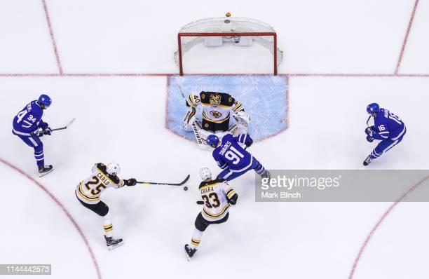 John Tavares Mitch Marner and Auston Matthews of the Toronto Maple Leafs go the net against Tuukka Rask Zdeno Chara and Brandon Carlo of the Boston...