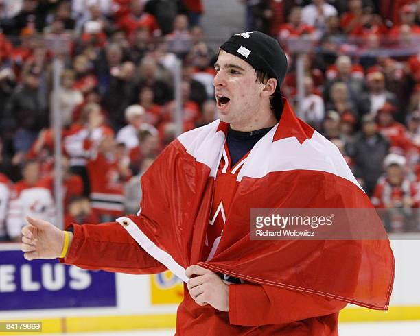 John Tavares of Team Canada skates with a Canadian flag wrapped around him during post game ceremonies after defeating Team Sweden at the Gold Medal...