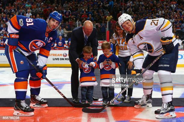 John Tavares of the New York Islanders and Kyle Okposo of the Buffalo Sabres pose for a photo with Austin and Joseph Tuozzolo the sons of SGT...