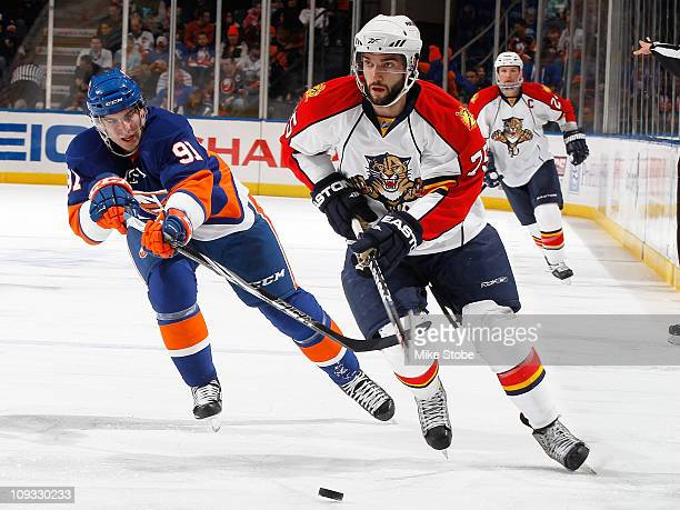 John Tavares of the New York Islanders and Scott Timmins of the Florida Panthers skate for posession of a loose puck on February 21 2011 at Nassau...