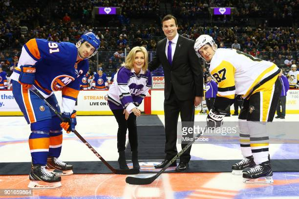 John Tavares of the New York Islanders and Sidney Crosby of the Pittsburgh Penguins pose for a ceremonial puck drop with Luke and Stephanie...