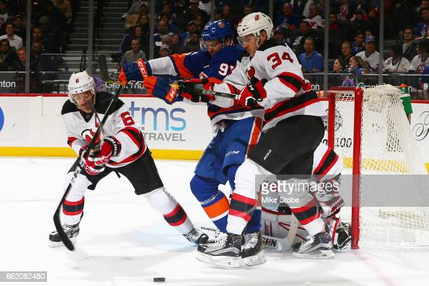 John Tavares of the New York Islanders and Steven Santini of the New Jersey Devils battle for the puck at the Barclays Center on March 31 2017 in...