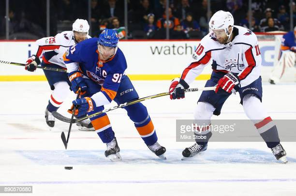 John Tavares of the New York Islanders carries the puck over the blueline as Brett Connolly and Devante SmithPelly of the Washington Capitals give...