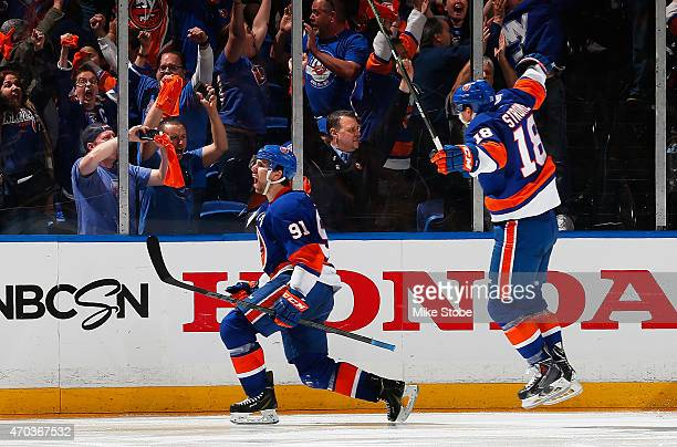 John Tavares of the New York Islanders celebrates his game winning goal in overtime with teammate Ryan Strome during the game against the Washington...