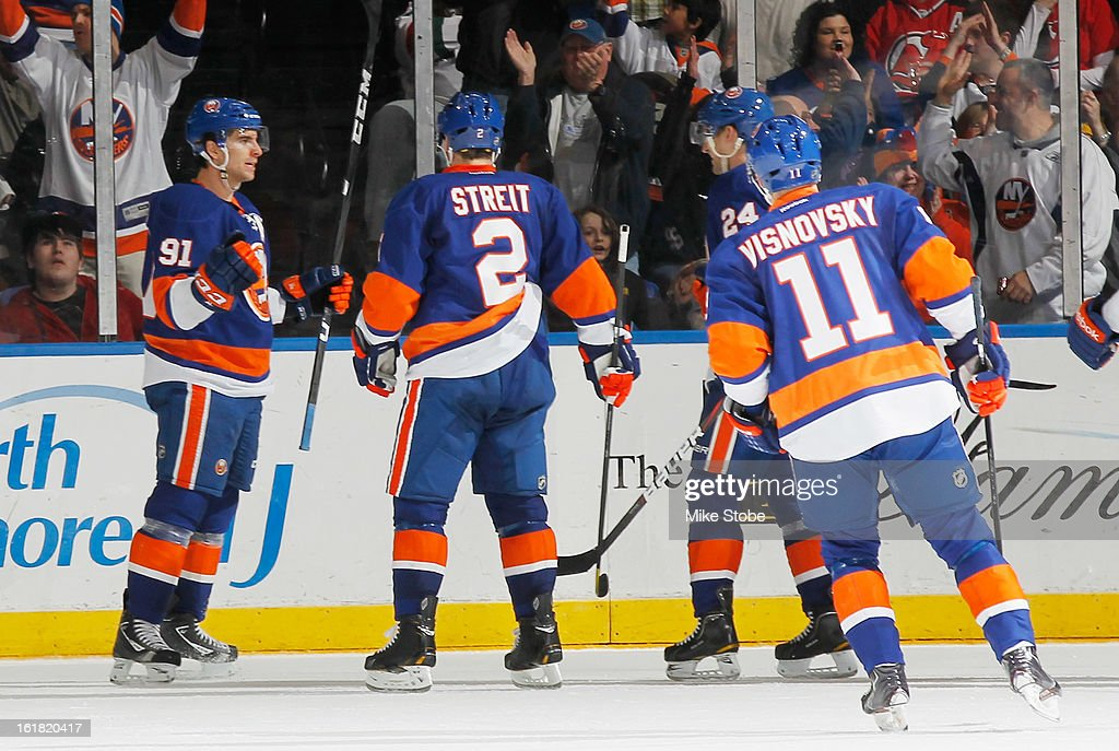 John Tavares #91 of the New York Islanders celebrates his goal against the New Jersey Devils with his teamattes at Nassau Veterans Memorial Coliseum on February 16, 2013 in Uniondale, New York. The Islanders defeated the Devils 5-1.