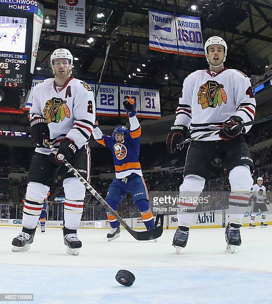 John Tavares of the New York Islanders celebrates the overtime game winning goal by Kyle Okposo as Duncan Keith and Niklas Hjalmarsson of the Chicago...