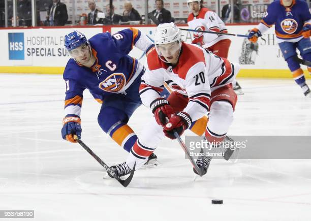 John Tavares of the New York Islanders checks Sebastian Aho of the Carolina Hurricanes during the second period at the Barclays Center on March 18...