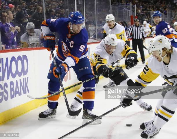 John Tavares of the New York Islanders controls the puck as Patric Hornqvist of the Pittsburgh Penguins reaches in during the first period at the...