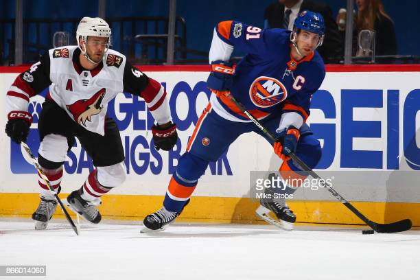 John Tavares of the New York Islanders eludes Niklas Hjalmarsson of the Arizona Coyotes in the offensive zone at Barclays Center on October 24 2017...