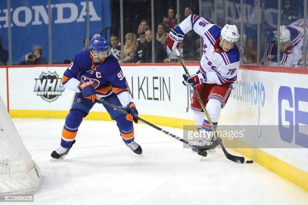 John Tavares of the New York Islanders fights for the puck against Brady Skjei of the New York Rangers in the second period during their game at...