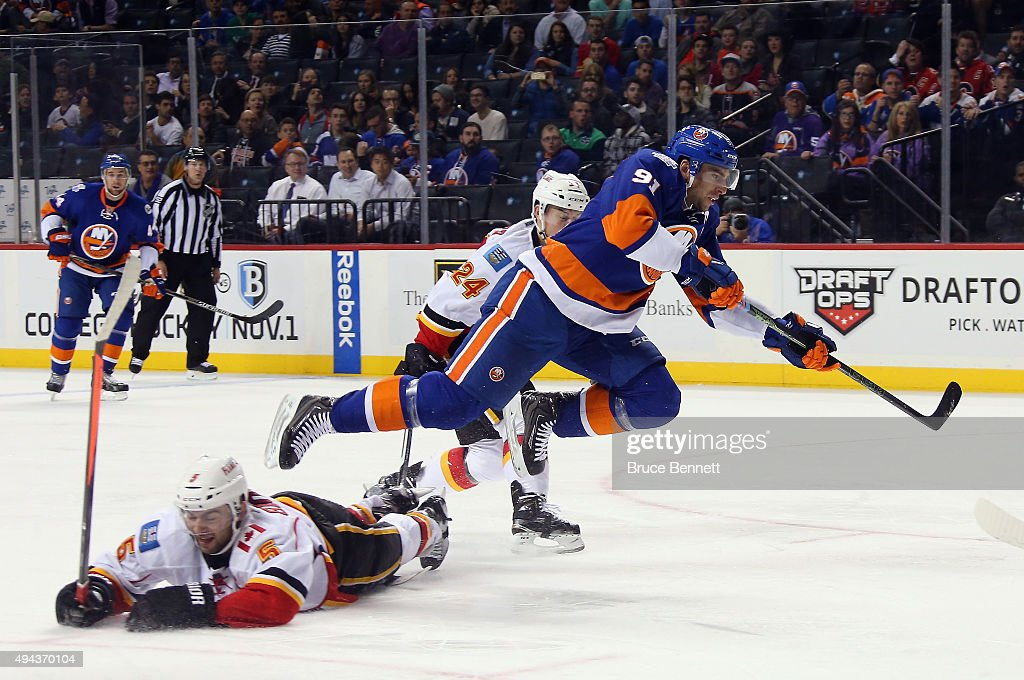 John Tavares #91 of the New York Islanders gets off a shot while being checked by Mark Giordano #5 and Jiri Hudler #24 of the Calgary Flames during the second period at the Barclays Center on October 26, 2015 in the Brooklyn borough of New York City.