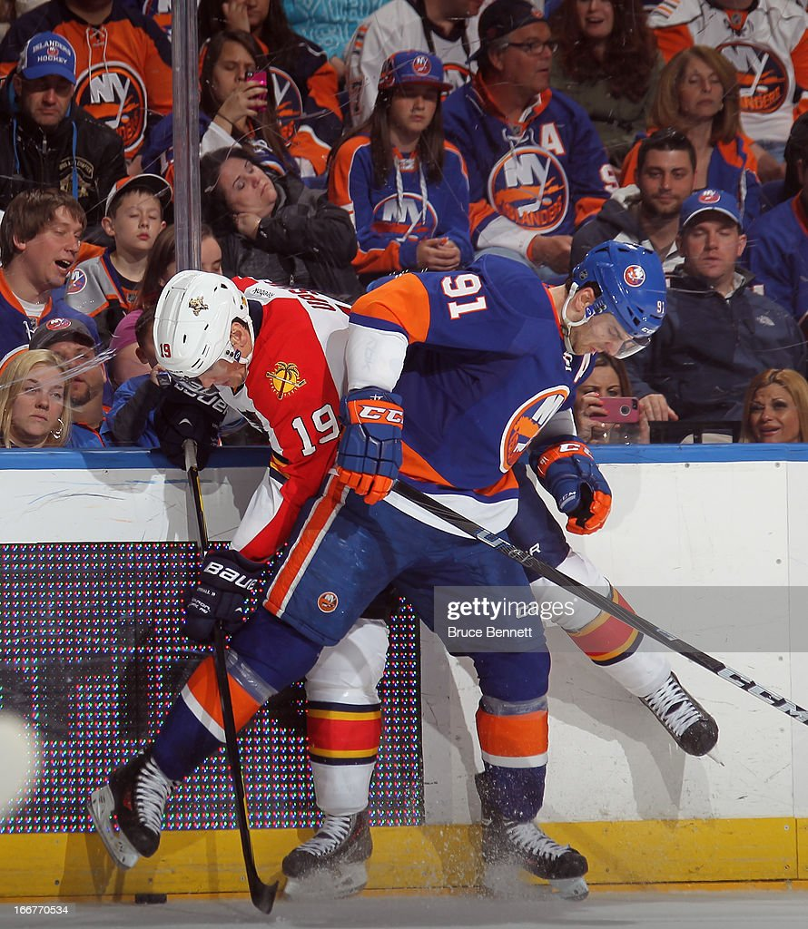 John Tavares #91 of the New York Islanders hits Scottie Upshall #19 of the Florida Panthers into the boards during the second period at the Nassau Veterans Memorial Coliseum on April 16, 2013 in Uniondale, New York.