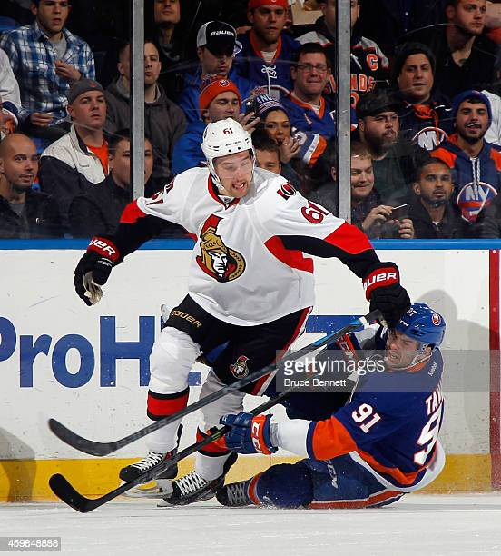 John Tavares of the New York Islanders hits the ice as Mark Stone of the Ottawa Senators moves up ice during the first period at the Nassau Veterans...