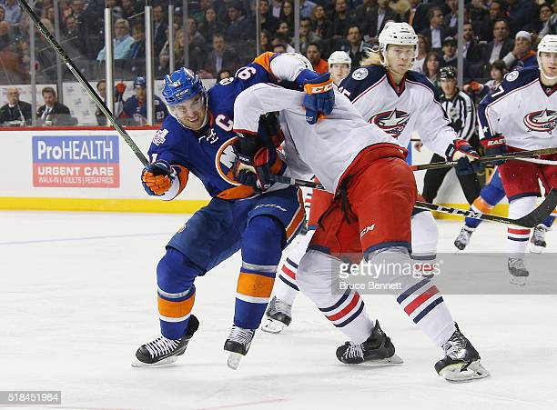 John Tavares of the New York Islanders is held up by Seth Jones of the Columbus Blue Jackets during the second period at the Barclays Center on March...