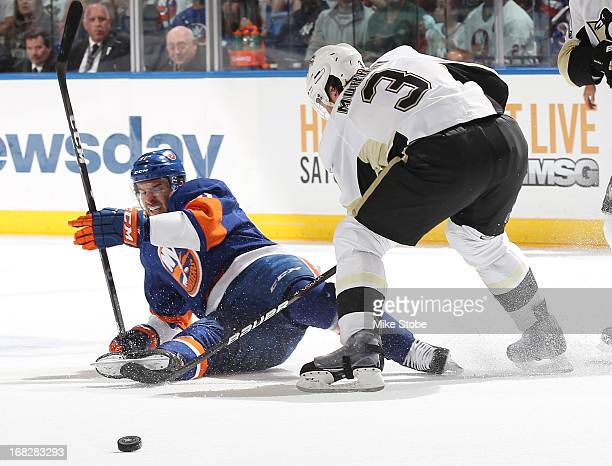 John Tavares of the New York Islanders is knocked to the ice by Douglas Murray of the Pittsburgh Penguins in Game Four of the Eastern Conference...