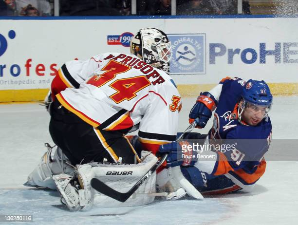 John Tavares of the New York Islanders is stopped by Miikka Kiprusoff of the Calgary Flames at the Nassau Veterans Memorial Coliseum on December 29,...
