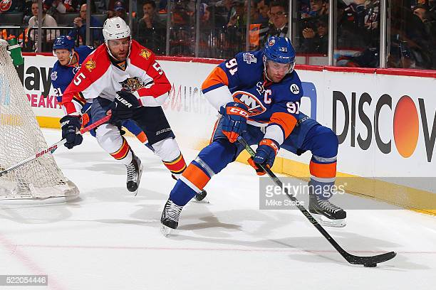 John Tavares of the New York Islanders plays the puck against Aaron Ekblad of the Florida Panthers in Game Three of the Eastern Conference...
