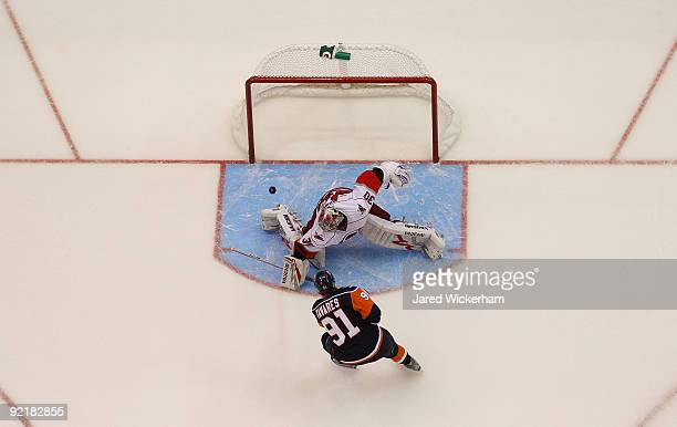 John Tavares of the New York Islanders scores the winning goal in the shootout on Cam Ward of the Carolina Hurricanes during the game on October 21...