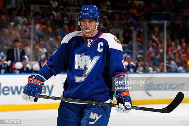 John Tavares of the New York Islanders skates against the San Jose Sharks at Nassau Veterans Memorial Coliseum on October 16 2014 in Uniondale New...
