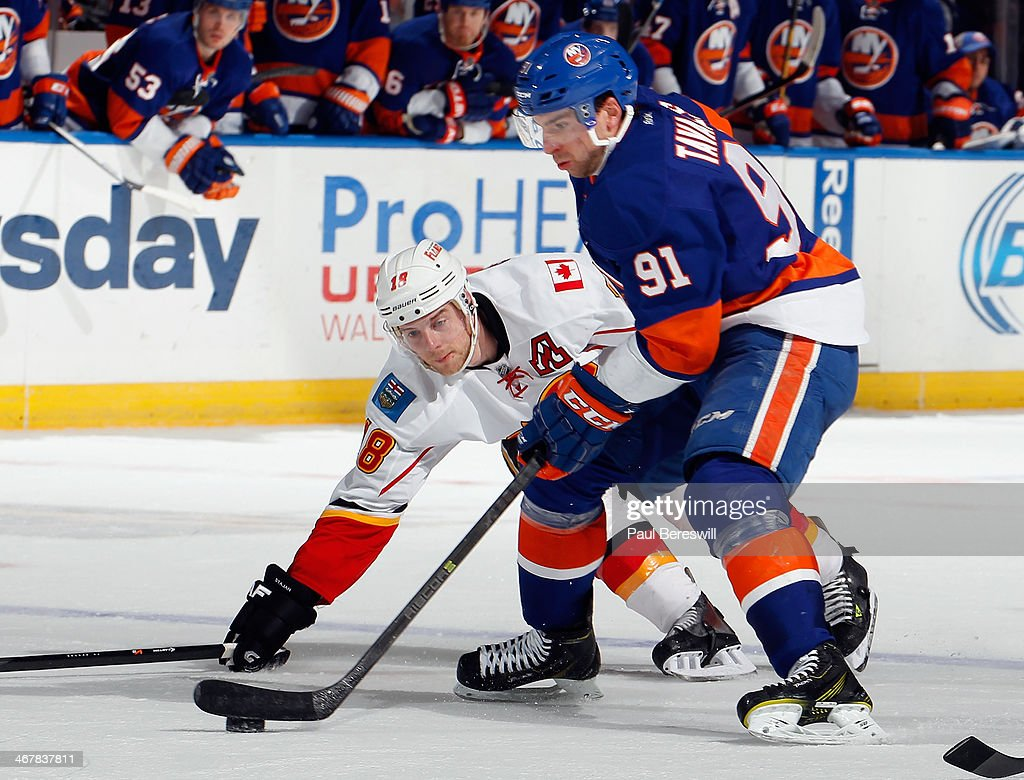 John Tavares #91 of the New York Islanders skates past Matt Stajan #18 of the Calgary Flames during an NHL hockey game at Nassau Veterans Memorial Coliseum on February 6, 2014 in Uniondale, New York.