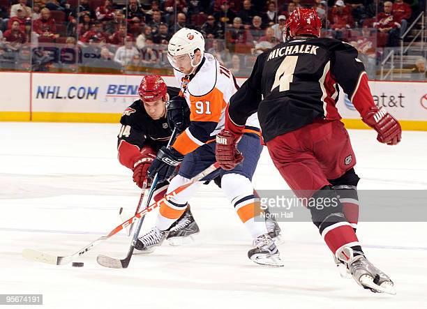 John Tavares of the New York Islanders skates with the puck against Taylor Pyatt and Zbynek Michalek of the Phoenix Coyotes on January 9 2010 at...