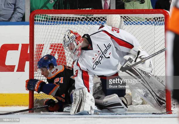 John Tavares of the New York Islanders slides into the net and joins Philipp Grubauer of the Washington Capitals at the Nassau Veterans Memorial...