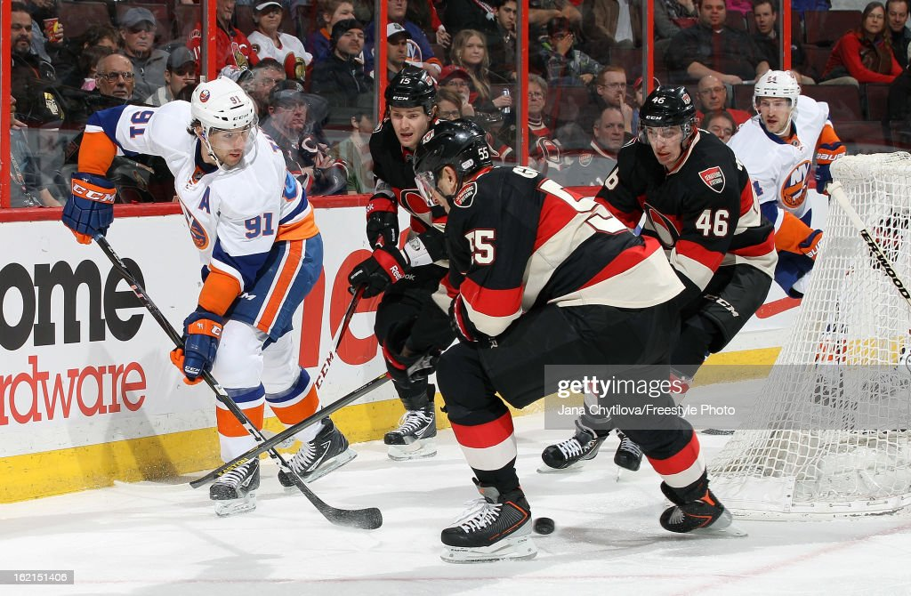 John Tavares #91 of the New York Islanders threads a pass through the legs of Sergei Gonchar #55 of the Ottawa Senators, during an NHL game at Scotiabank Place on February 19, 2013 in Ottawa, Ontario, Canada.