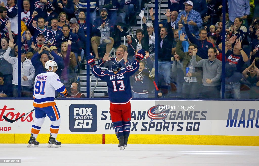 John Tavares #91 of the New York Islanders watches as Cam Atkinson #13 of the Columbus Blue Jackets celebrates after scoring a goal during the first period on October 6, 2017 at Nationwide Arena in Columbus, Ohio.