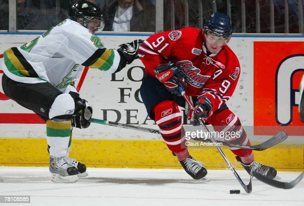 John Tavares of the Oshawa Generals tries to fire a shot around the coverage of Andrew Wilkins of the London Knights in a game on November 23, 2007...