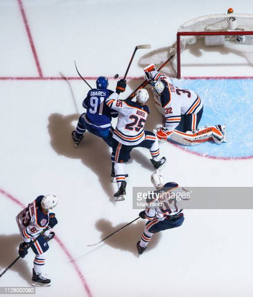 John Tavares of the Toronto Maple Leafs battles for a loose puck against Darnell Nurse of the Edmonton Oilers and Anthony Stolarz during the third...