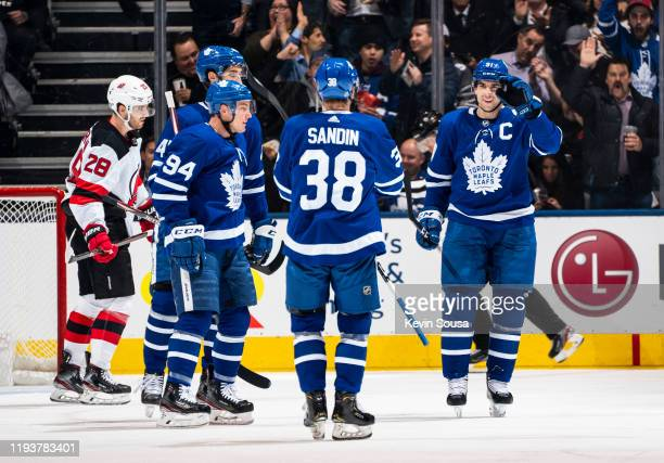 John Tavares of the Toronto Maple Leafs celebrates his goal against the New Jersey Devils with teammates Rasmus Sandin and Tyson Barrie during the...