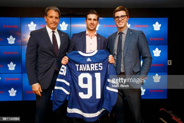 John Tavares of the Toronto Maple Leafs poses with his jersey after signing with the Maple Leafs, beside Kyle Dubas, General Manager of the Toronto...