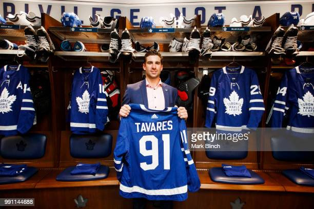 John Tavares of the Toronto Maple Leafs poses with his jersey in the dressing room after he signed with the Toronto Maple Leafs at the Scotiabank...