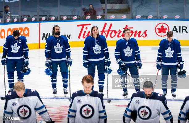 John Tavares, Zach Bogosian, Justin Holl, Zach Hyman, and Mikko Lehtonen of the Toronto Maple Leafs stand for the national anthem during the first...