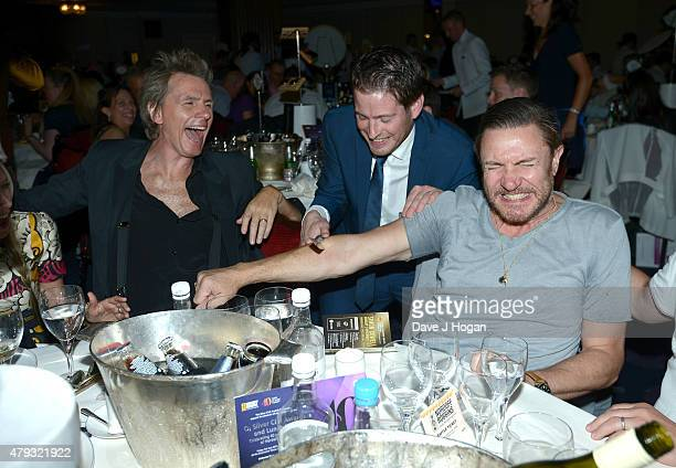 John Taylor and Simon Le Bon from Duran Duran with table magican at the Nordoff Robbins O2 Silver Clef awards at the Grosvenor House Hotel on July 3...