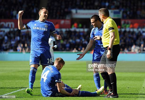 John Terry and Cesar Azpilicueta of Chelsea remonstrate with Referee Phil Dowd after teammate Andre Schurrle is fouled by Chico Flores of Swansea...
