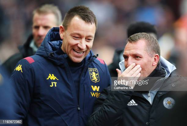 John Terry, Assistant Head Coach of Aston Villa speaks with Brendan Rodgers, Manager of Leicester City prior to the Premier League match between...